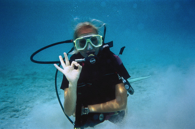 Woman Underwater in Scuba Gear Making Ok Sign