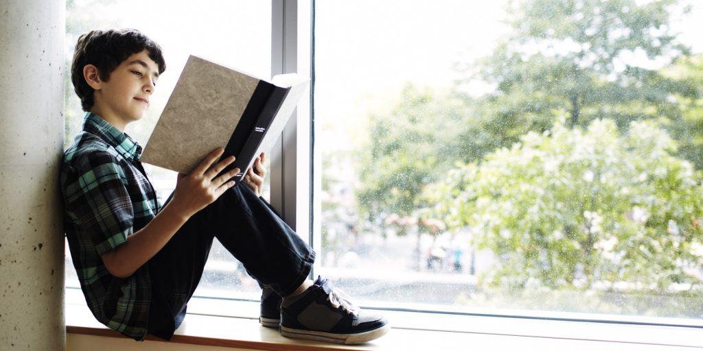 Boy reading book sitting in window nook